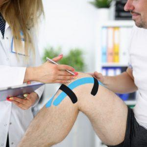 medico-examina-rodilla-lesionada-paciente-cinta-kinesio_151013-13691